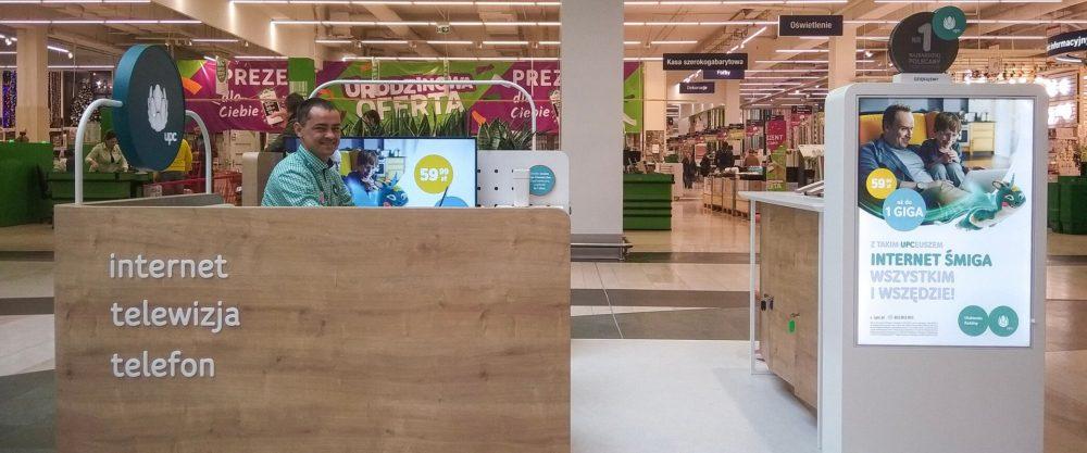 Po wprowadzeniu nowego konceptu salonów sprzedaży w Warszawie, Sosnowcu, Gdańsku i Bydgoszczy, UPC Polska postawiło teraz także na mobilne rozwiązanie w największym centrum handlowym w Polsce – Westfield Arkadia. Stoisko zapewni nie tylko wygodną i kompleksową obsługę klientów, ale także możliwość bezpośredniego kontaktu z nowoczesnymi rozwiązaniami operatora w zakresie usług internetowych, mobilnych oraz cyfrowej rozrywki. Goście odwiedzający centrum handlowe Westfield Arkadia na stoisku UPC Polska zyskują możliwość przetestowania usług oraz urządzeń znajdujących się w ofercie, m.in. smartfonów marki Samsung, które dołączyły do portfolio operatora wraz z odświeżoną ofertą usług mobilnych. Mogą także poznać możliwości platformy Horizon GO, dającej dostęp do ulubionych treści na wielu urządzeniach, także poza domem. Wyspa UPC Polska w Westfield Arkadia, największym centrum handlowym w Polsce, pozwoli nam być jeszcze bliżej naszych klientów, dając im możliwość poznania naszej wyjątkowej oferty superszybkiego internetu, najlepiej zintegrowanej telewizyjnej rozrywki i usług mobilnych, w połączeniu z najwyższej jakości obsługą. Jarosław Pijanowski, VP Sales & Care UPC Polska Koncept powstał we współpracy z pracownią Workplace Solutions Sp. z o.o. Forma wyspy nie przypomina standardowych stoisk w centrach handlowych. Półotwarta forma oferuje prywatność, przy jednoczesnym poczuciu otwartości, które zachęca klientów do odwiedzenia stoiska, przywodząc na myśl domową przestrzeń.